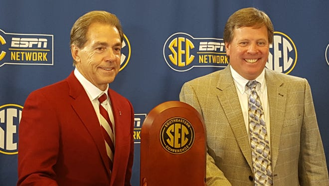 Alabama coach Nick Saban and Florida coach Jim McElwain pose with the SEC Championship game trophy Friday at the Georgia Dome in Atlanta.