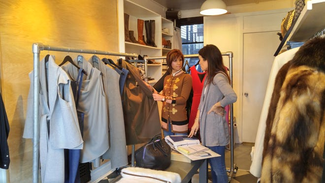 Hilary Arthur, right, owner of downtown boutique Arthur & Daughters, discusses merchandise with salesperson Stefanie Skippy.