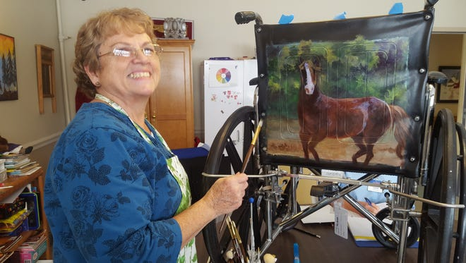 Beverly Garringer is shown painting the back of a wheelchair for a resident at Golden Living Center.  The Muncie Artist Guild is working with Laurie Lundsford at Golden Living Center to paint the wheelchairs in the Alzheimers' wing. A painting date planned for Feb. 20.