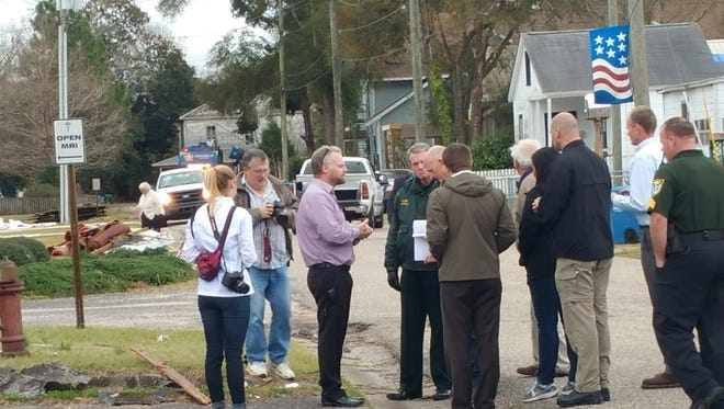 Gov. Rick Scott looks at a petition handed to him by Christian Bachman on Wednesday outside the Mayo Street Clinic in Century.