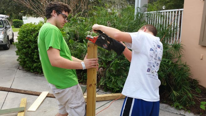 Eagle Scout William Jobes, left, and his helpers built a new house for the coyotes at Shy Wolf Sanctuary.