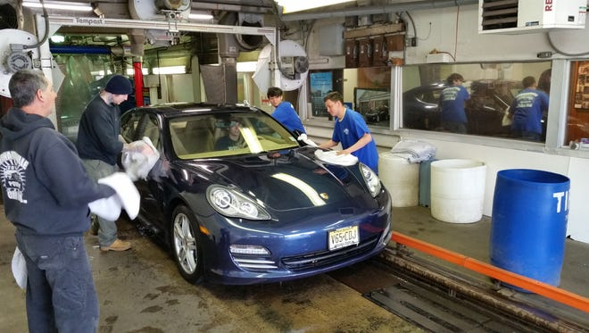 By machine and hand: employees wipe down a Porsche that is pulled through the tunnel at the Bernardsville Car Wash.