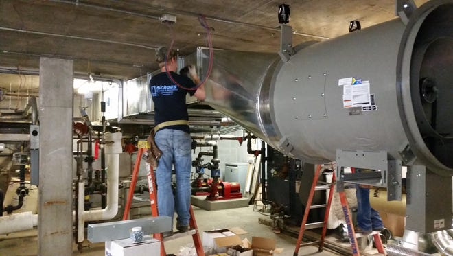 A Schaus Roofing & Mechanical Contractors employee performs work on the heating and air conditioning system at Manitowoc Public Utilities.