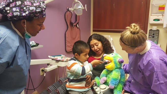 Wilson County's Neighborhood Health clinic will add dental services in January. Pictured are Michele Blackledge, dentist and Dental Services Director, left, and hygienist Stephenie Graham, right, with a mother and child at Neighborhood Health's East Side clinic in Davidson County.