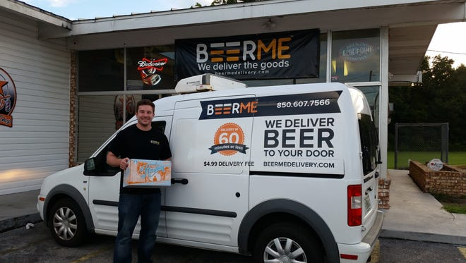 BeerMe Delivery co-owner Drew Ruff stands in front of one of his delivery vehicles at his shop in Pensacola. The beer and wine shop delivers within a 15-mile radius of its North Palafox Street location.