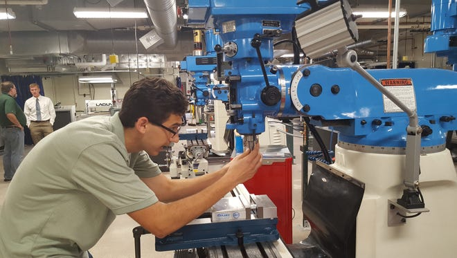 Wausau East senior Brennen Pozorski demonstrates an adjustment on a new, manually-operated mill at the high school on Sept. 9, 2016.