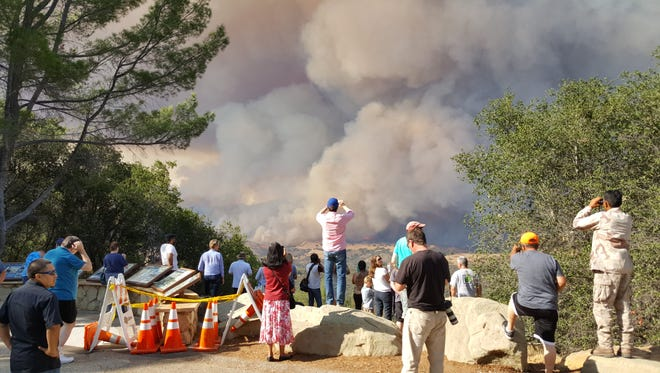 Onlookers are drawn to the San Marcos lookout to see and take photos of the smoke and flames of the Rey Fire.
