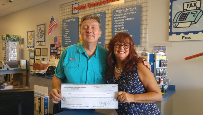 VBCBA board member Cindy Hejlik accepts a $350 check from Marc Richard, owner of Postal Connections, representing profits from the company's sixth anniversary day.
