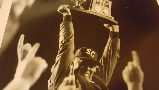 Walt Criner lifts a trophy over his head as head coach of Snow College in 1985.