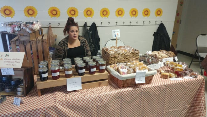 Alyssa Regan sells jams made by her mom Diana at a craft show. Diana Regan will sell handmade baked goods and jams at the upcoming holiday pop-up market in Milford.