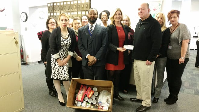 Staff members from the Cumberland County Clerk's Office present Steve Plevins (right), co-founder of Project Thanksgiving, with a check and food donations to support Project Thanksgiving.