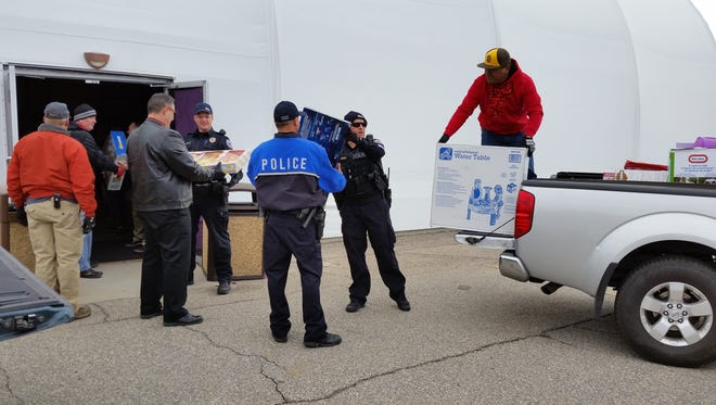 Members of the Mesquite Police and Fire Departments help unload toys at the 12th annual Golf Fore Kids event Thursday, Dec. 8, 2016.