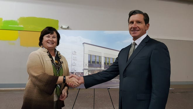 Salem Mayor Anna Peterson, left, shakes hands with Dino Andereggen, Pacific Office Automation VP of the Oregon market. Pacific Office Automation has announced plans to move to downtown Salem, and will renovate the building located at 260 Liberty St. NE.