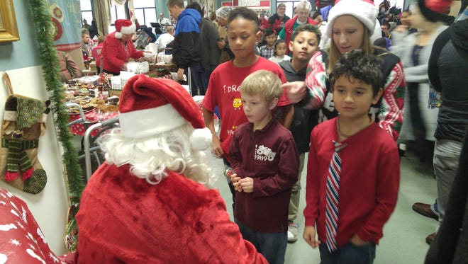 Santa Claus hands out presents at NOEL Christmas Breakfast as St. Paul's By the Sea.