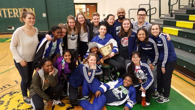 The Montclair High School girls' fencing team and coaches celebrate after winning a second-straight epee squad New Jersey state title this past Saturday at North Hunterdon Regional High School.