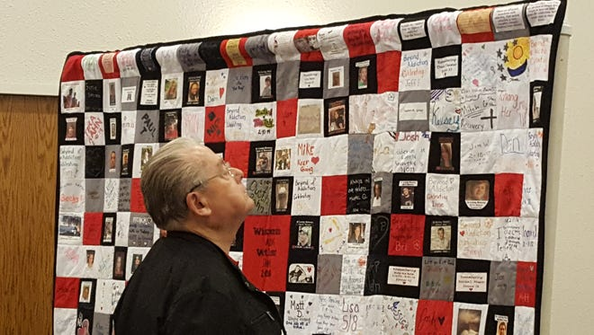 An attendee looks at a quilt featuring the stories of those affected by drug addition during a kick-off event Monday, April 17, 2017, for the Winnebago County Drug & Alcohol Coalition at LaSure's Banquet Hall in Oshkosh.