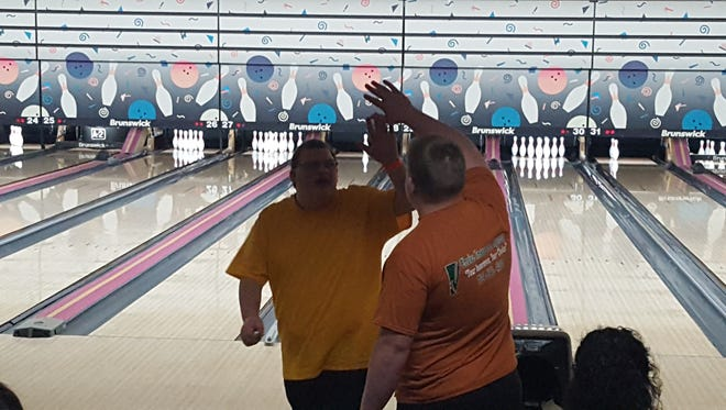 Exchanging a high five are a Special Olympian bowler (left) and Livonia Churchill's Brennan Mikel.