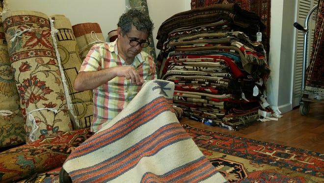 Morteza Kandi, owner of Kandi's Gallery, sits on a Persian rug while he repairs a Navajo rug inside his Bernardsville studio. Kandi was born in Iran and learned about rugs from his mother. He moved his studio from Manhattan to Bernardsville in September.