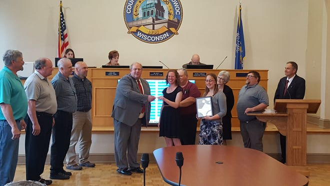 Manitowoc County Board Chairman Jim Brey presents Manitowoc County Historical Society Executive Director Amy Meyer with a proclamation at its meeting Tuesday at the Heritage Center.
