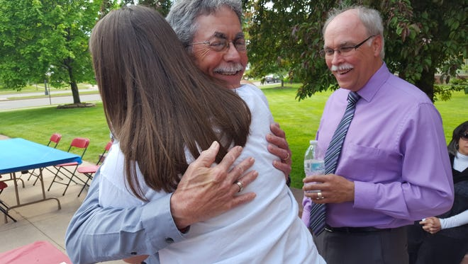 Devery Quandt hugs his former student Mikayla Tomsyck at his retirement party on Thursday at Newman Catholic High School and Middle School as Mike Tomsyck looks on.