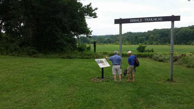 Mathew Marty shows a hiker a plaque explaining the natural history of Donald County Park in Dane County, about five miles south of Mount Horeb.