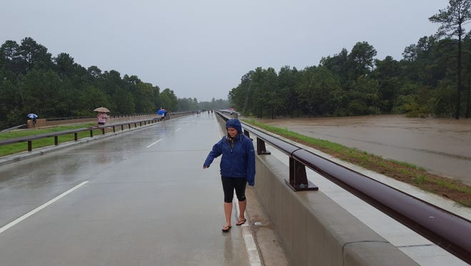 Julie Niethammer, a former Dexter resident, stands on an overpass in Texas on Monday, Aug. 28, 2017. A 4-5 foot wide stream is typically 20-30 feet below the bridge, but the water rose during Hurricane Harvey to touch the underside of the bridge, closing the road. Niethammer is scrambling to make alternate plans after the venue set for her Sept. 3 Houston wedding flooded.