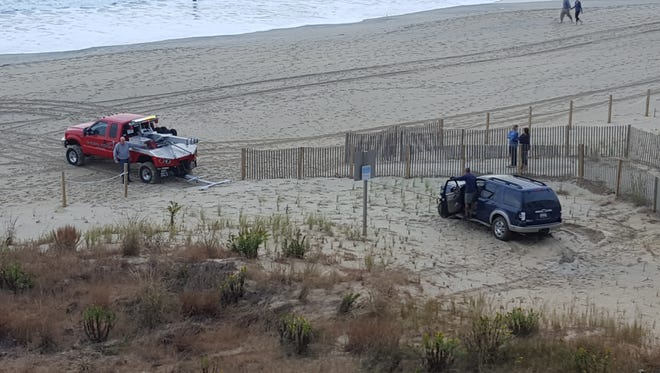 A tow truck pulls an SUV off the 99th Street dune after the vehicle crashed there, Ocean City police say.
