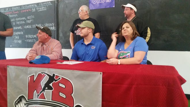 Noah Banks, center, is joined by his father (left), mother Liza (right) and former coaches from West Florida Tech at his college signing at KB Performance Training on Dec. 20, 2017. Banks signed with the Florida Gators.