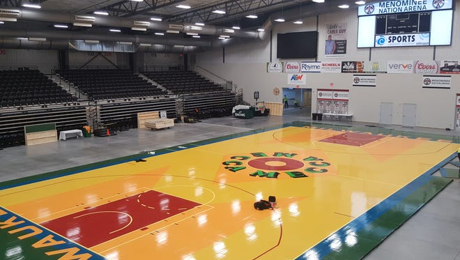 Crews install a new floor Thursday, Dec. 28, 2017, at the Menominee Nation Arena in Oshkosh. The floor is a replica of the Robert Indiana-designed basketball court used at the MECCA.