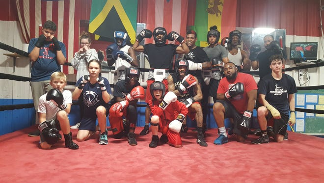 Members of the ROUND 13 boxing gym in Palm Bay pose during a training session for the upcoming match.