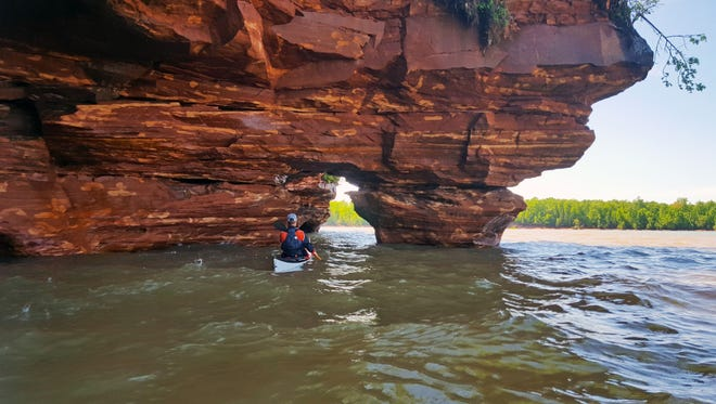 Jamiah Mahoney, a guide with Living Adventure, kayaks through a sea cave on Sand Island in the Apostle Islands National Lakeshore.