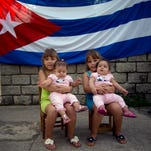 Six-year-old twins Asley and Aslen Velazquez hold eight-month-old twins Tiffani and Stessany Valles as they pose for portraits in front a Cuban flag on their street in Havana, Cuba, on Sept. 29, 2013.
