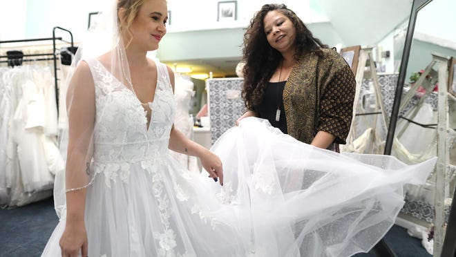 Alisha Alsbrook, right, the owner of Wedding Cycle, works with model Bethany Frye to try on a wedding dress at Alsbrooks's shop in the Thornebrook Village in Gainesville on Wednesday. In the wake of protests of police brutality in the United States following the death of George Floyd, and the subsequent call-to-action on social media for people to shop at Black-owned businesses, Alsbrook said she has received overwhelming support from previous and current customers.