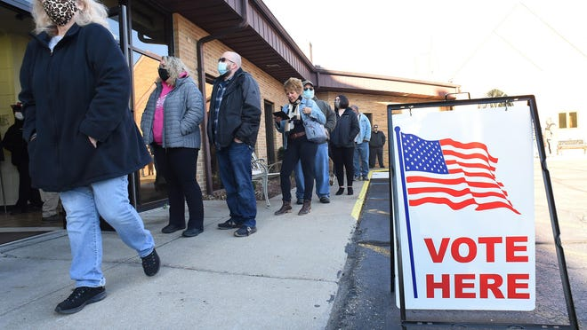 Residents of the City of Monroe wait in line Tuesday morning to vote in the general election.
