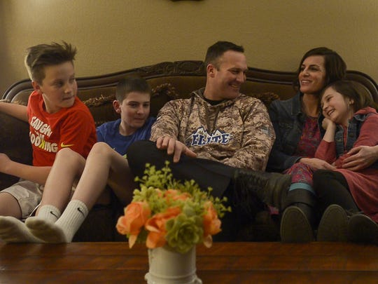 Fort Collins Police Services Officer Chris Renn and his family sit in their living room during an interview on Thursday, Feb. 15, 2018, in Johnstown, Colo.