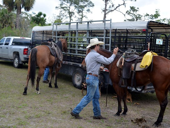 Cowboys in Immokalee saddle up their horses.