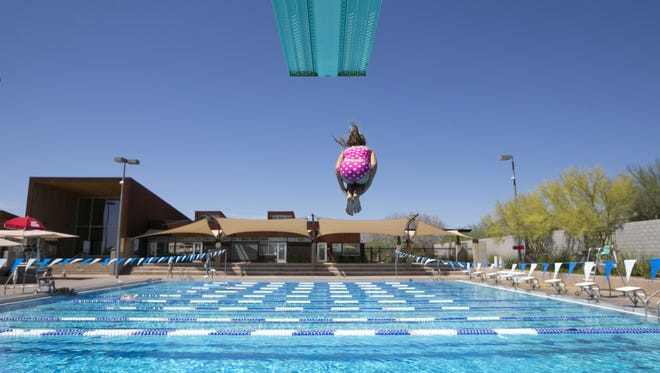 A girl jumps off a high diving board at the McDowell Mountain Ranch Aquatic & Fitness Center in Scottsdale on Saturday, May 3, 2014.