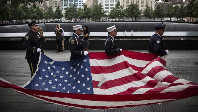 Members of the New York Police Department, Fire Department of New York and Port Authority Police Department carry a US flag at the beginning of the memorial observances held at the site of the World Trade Center in New York on Sept. 11, 2014. This year marks the 13th anniversary of the September 11th terrorist attacks that killed nearly 3,000 people at the World Trade Center, Pentagon and on Flight 93.