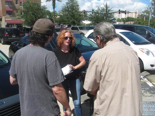 Clinton volunteer Theresa Darlington (center) tries