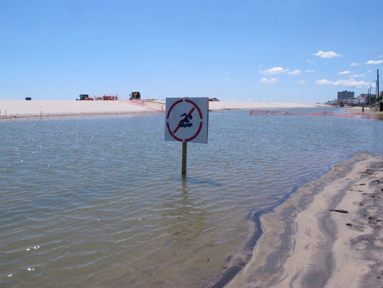 This July 31, 2017 photo shows a no swimming sign in