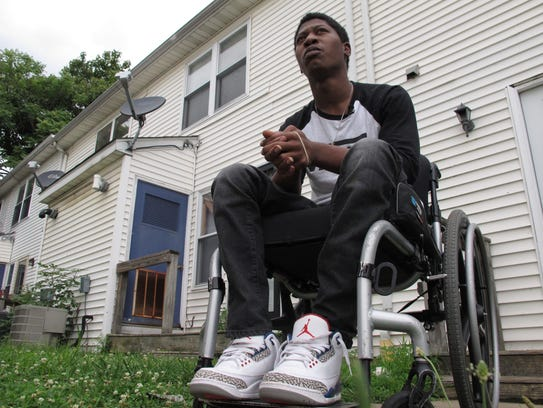 Rayquan Briscoe sits outside his home in Wilmington,