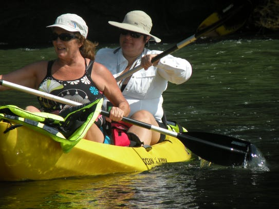 Paddlers head down the French Broad River during a
