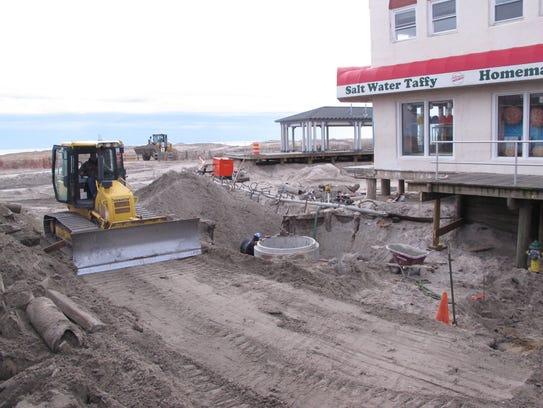 Workers replacing several blocks of boardwalk in Ocean
