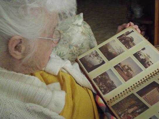 Erma Eash looks over a scrapbook of memories relating