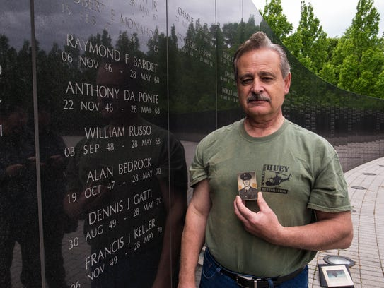 Standing at the memorial wall at the New Jersey Vietnam Veterans Memorial, George Da Ponte holds a portrait of his brother Anthony Da Ponte, who was killed in Vietnam in 1968.