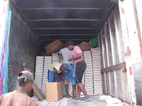 Employees of a Dominican egg company unload a truck