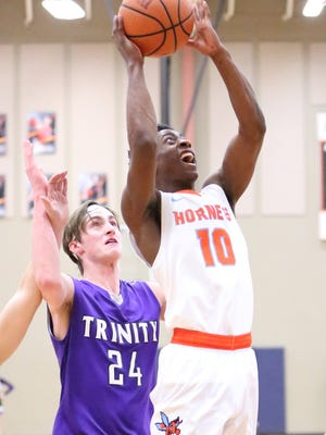 South Gibson's Cameron Mayberry jumps to shoot as TCA's Vann Bryant defends.