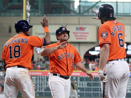Jun 3, 2016; Houston, TX, USA; Houston Astros first baseman Tyler White (13) celebrates with third baseman Luis Valbuena (18) and left fielder Jake Marisnick (6) after scoring against the Oakland Athletics in the first inning at Minute Maid Park. Mandatory Credit: Thomas B. Shea-USA TODAY Sports