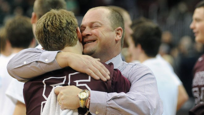 Head Coach Greg Woodard hugs Matt Weir after John Glenn's 76-72 Division II state finals victory over Akron St. Vincent-St. Mary in 2016. Woodard stepped down from his post on Wednesday after 19 years with his alma mater.