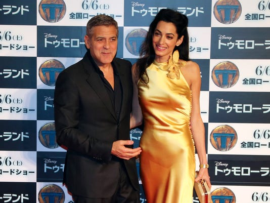 """U.S actor George Clooney and his wife Amal Clooney pose for photographers at a photo call for """"Tomorrowland"""" in Tokyo, Monday, May 25, 2015."""